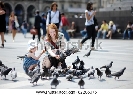 Young mother and daughter feeding pigeons