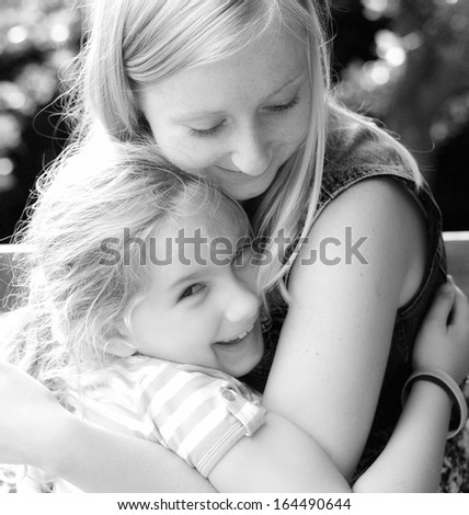 Young mother and daughter. Happy family in garden.
