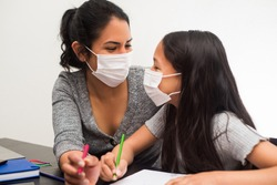 Young mother and daughter look at each other with complicity. Latin woman and kid working at home wears a prevention mask during virus infection.