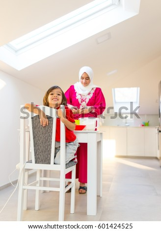 Young mother and happy playful son making muffins in kitchen #601424525