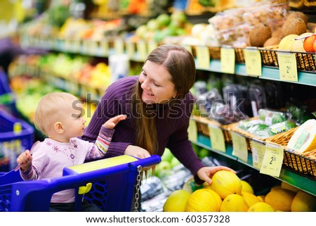 Young mother and her adorable baby daughter selecting fruits in supermarket