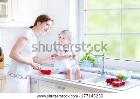 Young mother and her adorable curly toddler daughter washing vegetables together in a kitchen sink getting ready to make salad for lunch in a sunny white kitchen with a big garden view window