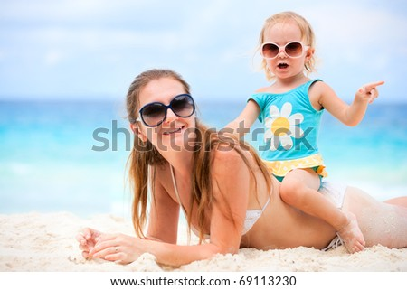 Young mother and her adorable little daughter on beach vacation