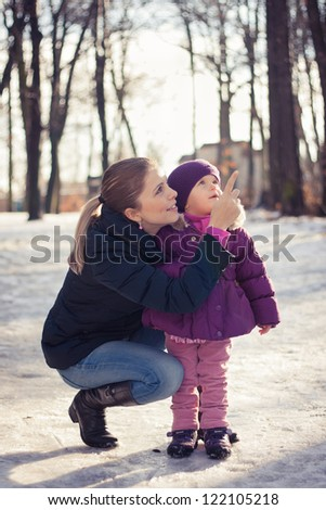 Young mother and her baby girl outdoors on a snowy winter day