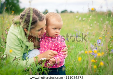 Young mother and her baby girl playing while outdoors on a walk Photo stock ©