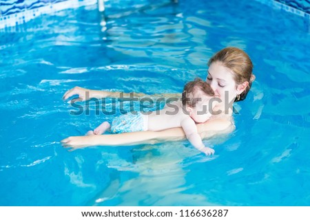 Young mother and her baby relaxing in a swimming pool
