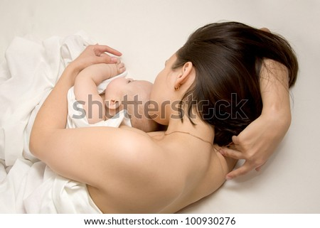 Young mother and her baby sleeping in bed