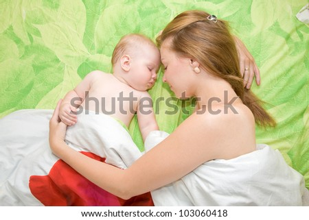 young mother and her baby sleeping in bed. - stock photo