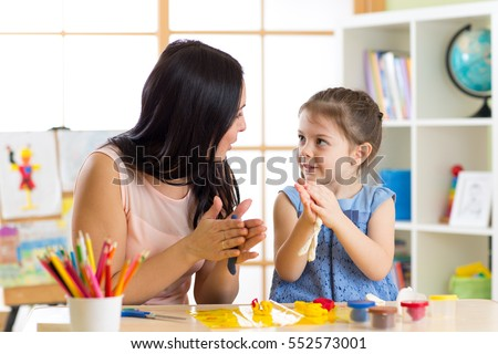 Young mother and her child daughter moulding together from plasticine snail