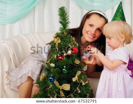 Young mother and her daughter are preparing for the holiday together. Happy New Year!