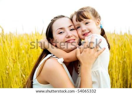 young mother and her daughter at the wheat field on a sunny day