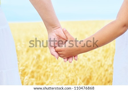 Young mother and her daughter holding hands
