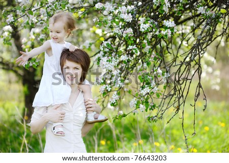 Young mother and her daughter in blossoming apple trees - stock photo