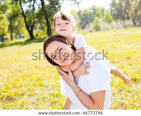young mother and her daughter in the park on a sunny autumn day