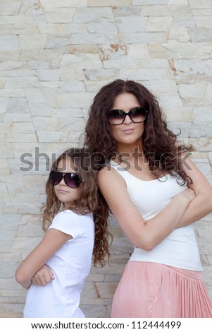 Young mother and her daughter standing back to back and smiling