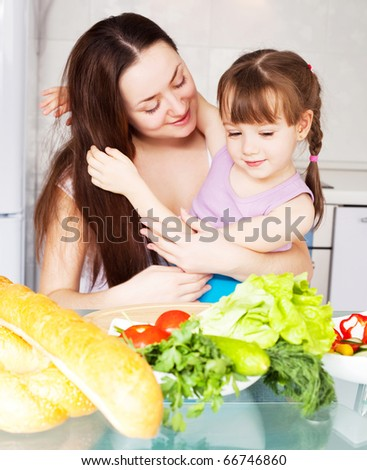 young mother and her five year old daughter cook together on the kitchen at home