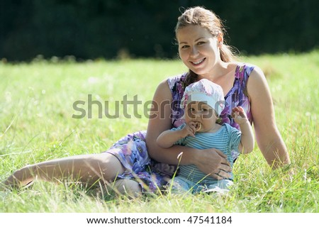 Young mother and her little baby are on green grass. They are smiling. Summer time. Sunny