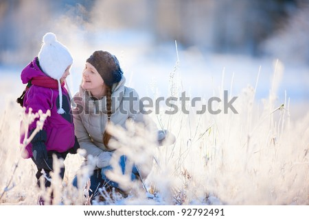 Young mother and her little daughter enjoying beautiful winter day outdoors