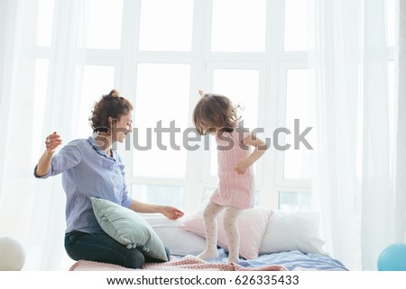 Young mother and her little daughter jumping on bed. Funny pillow fight. Soft pastel colors, pink and blue. Selective focus. Play together and enjoy the moment! Family time on weekend.  #626335433