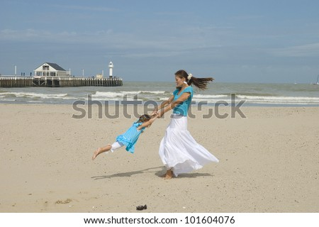 Young mother and her little daughter playing on the beach