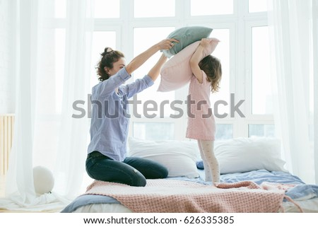 Young mother and her little daughter playing with cushions on bed. Funny pillow fight. Soft pastel colors, pink and blue. Selective focus. Play together and enjoy the moment! Family time on weekend.  #626335385