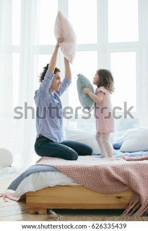 Young mother and her little daughter playing with cushions on bed. Funny pillow fight. Soft pastel colors, pink and blue. Selective focus. Play together and enjoy the moment! Family time on weekend.  #626335439