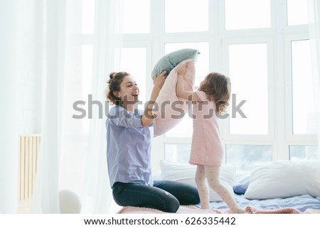 Young mother and her little daughter playing with cushions on bed. Funny pillow fight. Soft pastel colors, pink and blue. Selective focus. Play together and enjoy the moment! Family time on weekend.