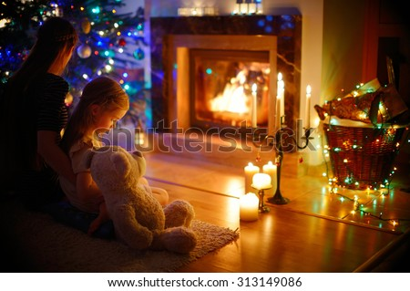Young mother and her little daughter sitting by a fireplace in a cozy dark living room on Christmas eve