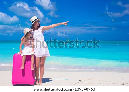 Young mother and her little daughter with luggage on tropical white beach
