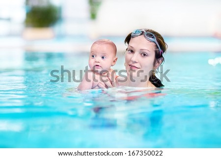 Young mother and her newborn baby having fun together in a swimming pool