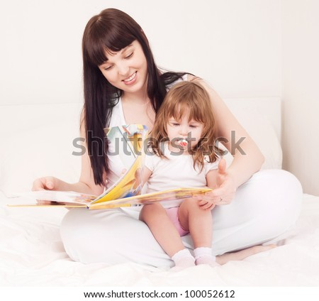 young mother and her one year old daughter reading a book in bed at home