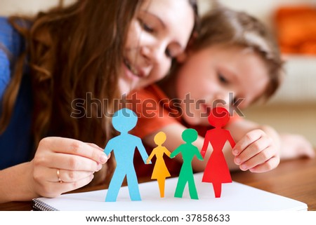 Young mother and her son holding figures of multicolored paper family