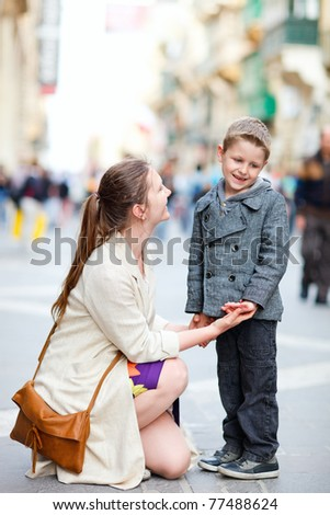 Young mother and her son outdoors on city street