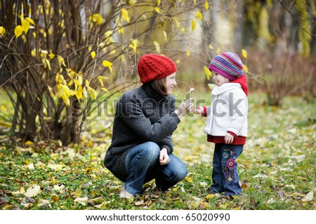 Young mother and her toddler girl having fun in autumn - stock photo