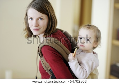 Young mother and her toddler girl in a baby carrier