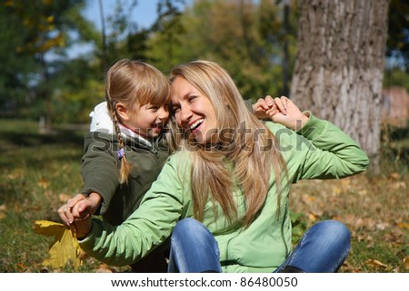 Young mother and her toddler girl in autumn fields - stock photo