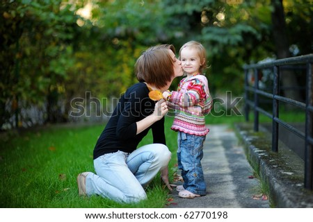 Young mother and her toddler having fun on autumn day