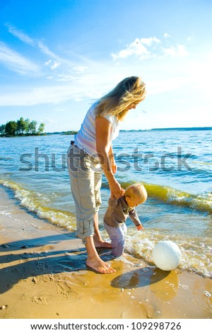 Young mother and her toddler walking on beach