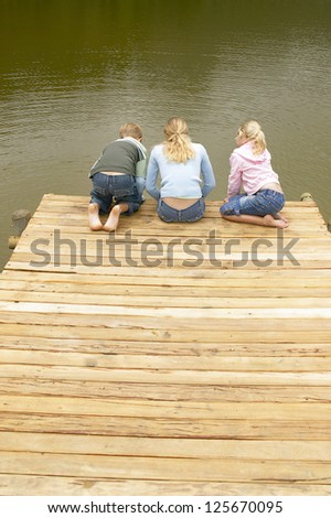 Young mother and her two children lean over the end of a wooden deck with their backs to the camera looking in to the water