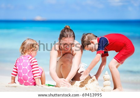 Young mother and her two kids building sand castle at beach