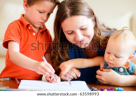 Young mother and her two kids drawing together