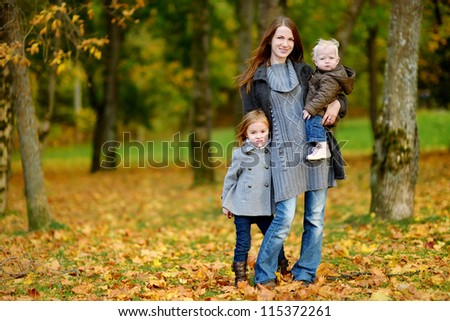 Young mother and her two little daughters at fall