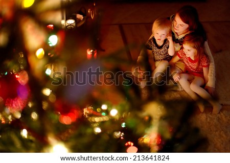 Young mother and her two little daughters sitting by a Christmas tree in a cozy dark living room on Christmas eve