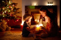 Young mother and her two little daughters sitting by a fireplace holding candles in a cozy dark living room on Christmas eve