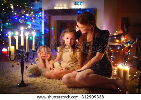 Young mother and her two little daughters sitting by a fireplace in a cozy dark living room on Christmas eve