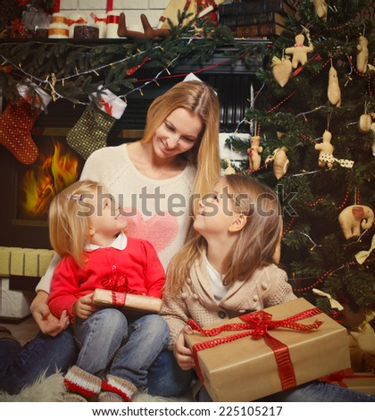 Young mother and her two little daughters with Christmas gifts by a Christmas tree in cozy living room with fireplace in winter