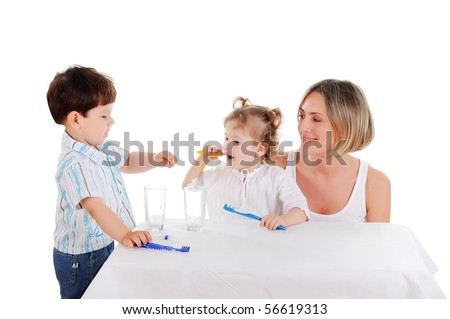 young mother and her young daughter and son brushing teeth on a white background