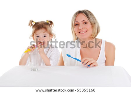young mother and her young daughter brush their teeth on a white background