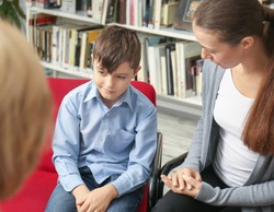 Young mother and little boy on meeting with teacher at school