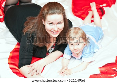 Young mother and little child laying on bed and smiling
